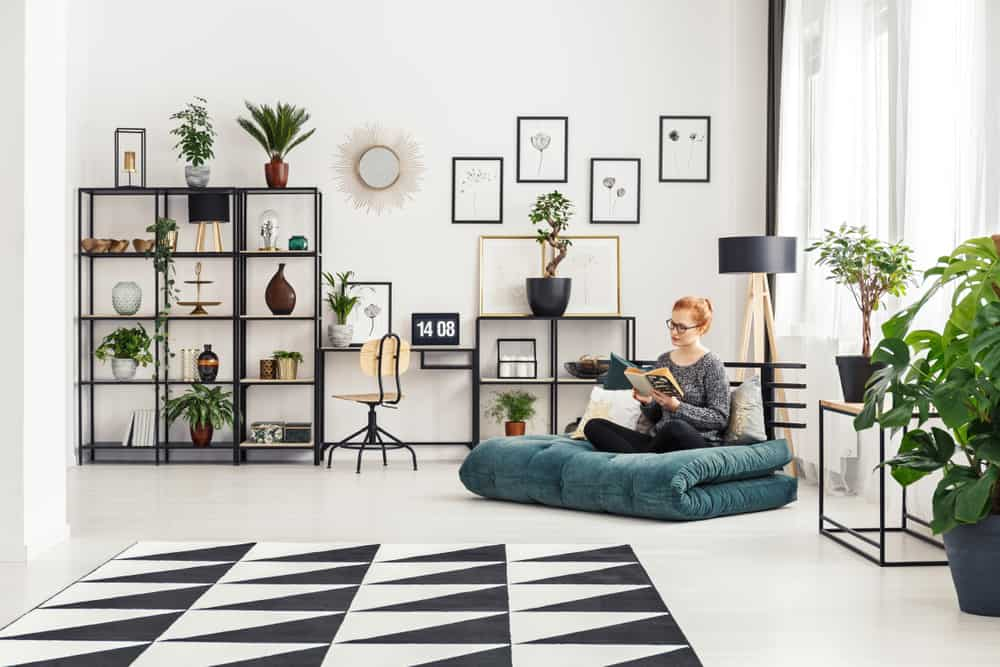 Girl in glasses sitting on a futon mattress and reading a book in bright interior with home office desk and fresh plants