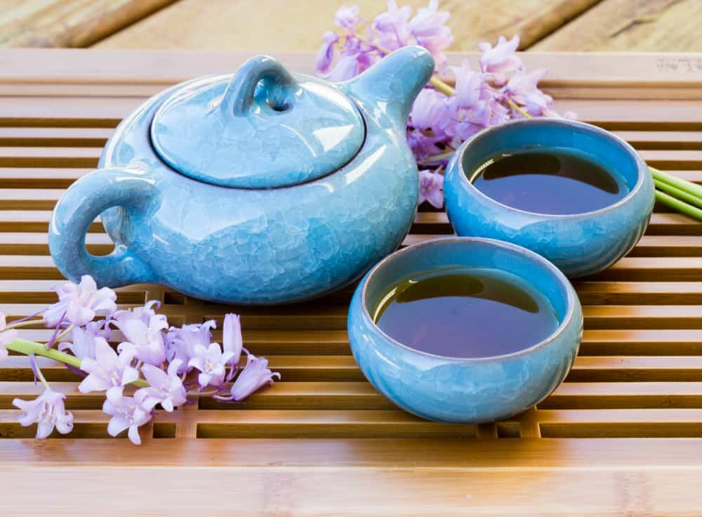 Royalty-free stock photo ID 1042765138 Blue ice crackle glazed ceramic tea pot with two cups of tea on a tray decorated with flowers