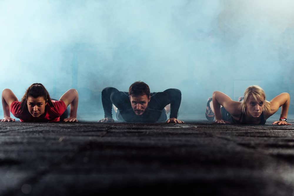 Attractive athletic young people doing press-ups in a gym surrounded by smoke