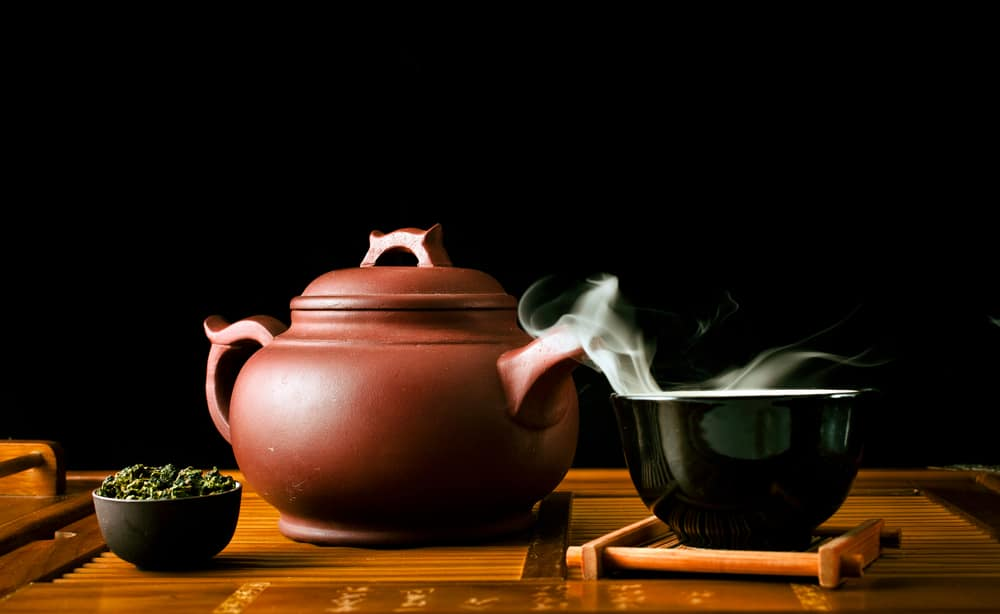 Chinese tea ceremony. Clay teapot with green oolong tea Tieguanyin on a black background and a cup of hot tea with vapour