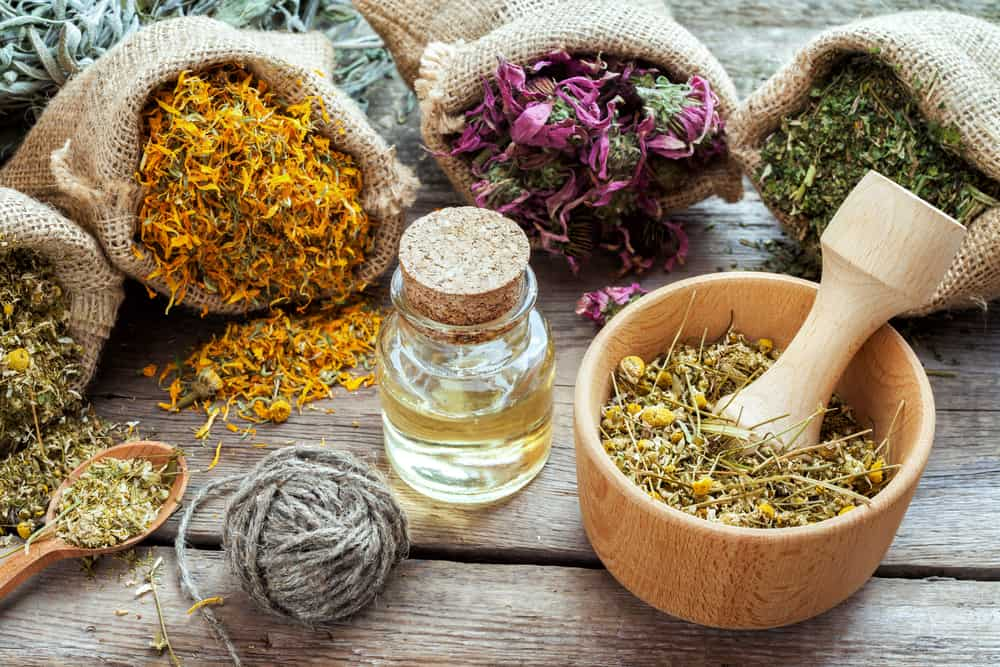Healing herbs in hessian bags, mortar with chamomile and essential oil on wooden table