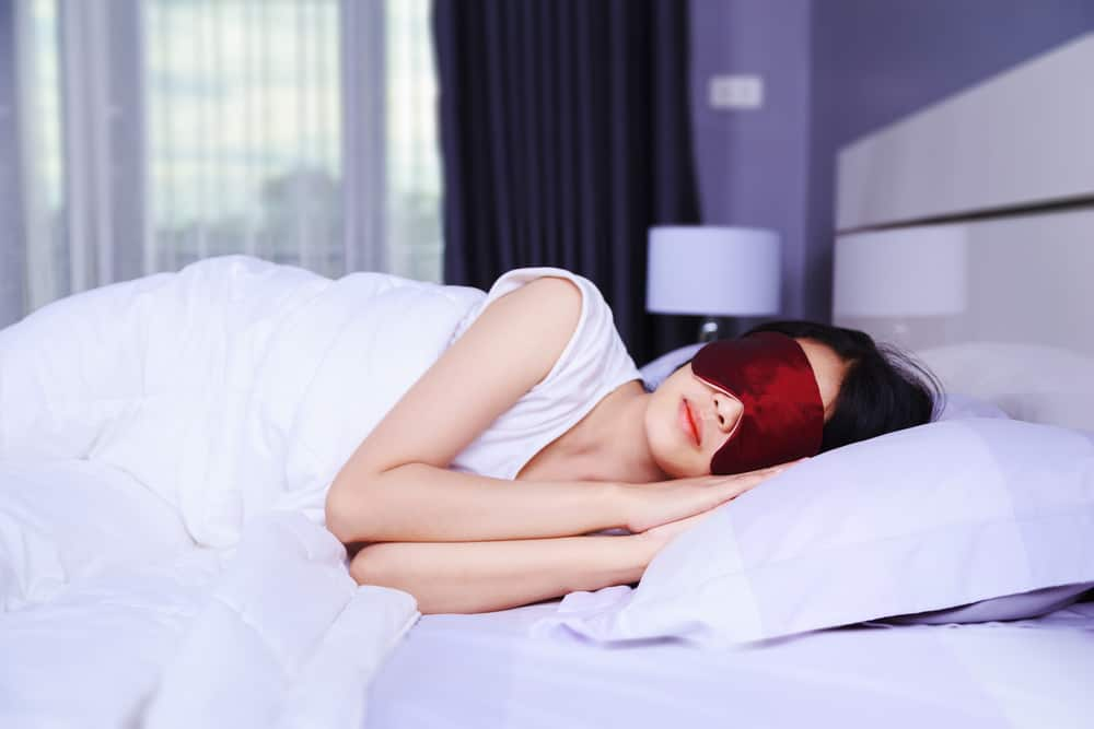 woman sleeping with eye mask on bed in the bedroom