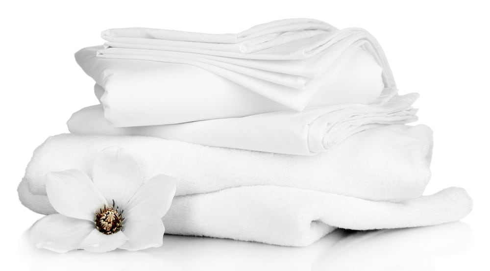 Stack of clean bedding sheets and towels isolated on whit