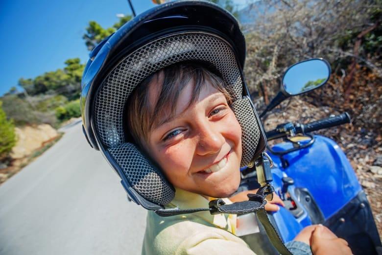 Little boy riding quad bike on Greece island