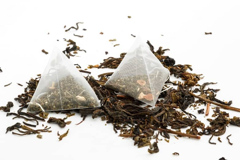 tea bags and loose green tea on a white background