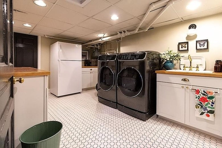 luxurious basement laundry room that includes extra features like full-featured cabinets, artwork, plants, or even a refrigerator