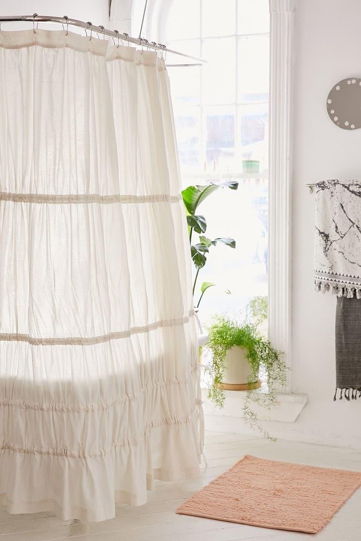 White Ruffled Curtains Around a Bathtub
